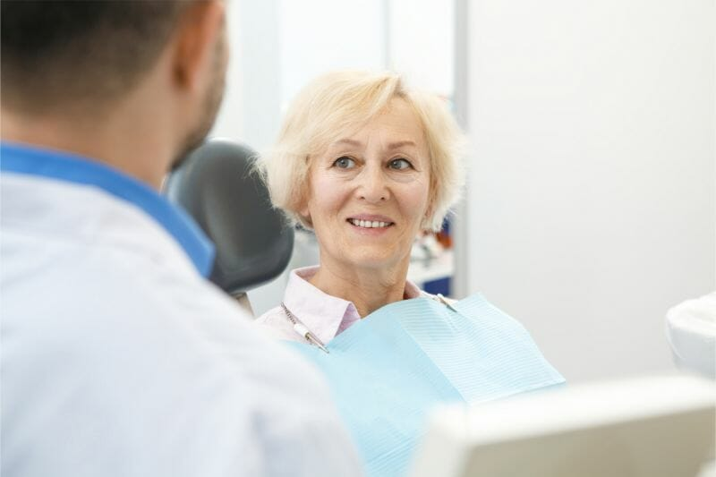 mature woman going over treatment with dentist