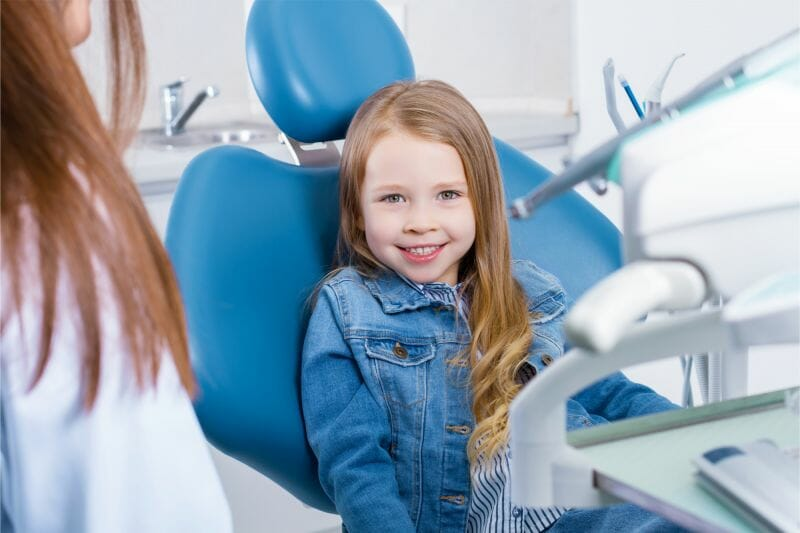 young girl at the dentist smiling